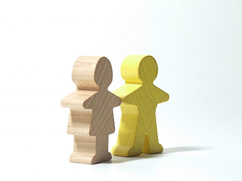 Two 3D, wooden icons of people standing together, one providing mental health support to the other